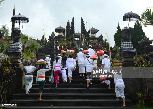 TOPSHOT Balinese people arrive at Besaki tempel to pray for Mount Agung during Purnama ceremony as Mount Agung is seen obscured by clouds in...