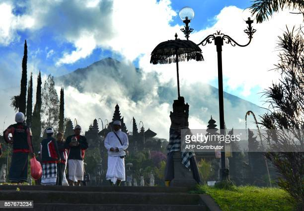 Balinese people pray for mount Agung during Purnama ceremony as Mount Agung volcano is seen obscured by clouds in the background at Besaki temple in...