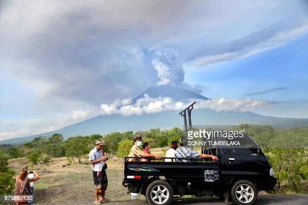 Balinese people ride on an open car past Mount Agung erupting seen from Kubu subdistrict in Karangasem Regency on Indonesia's resort island of Bali...