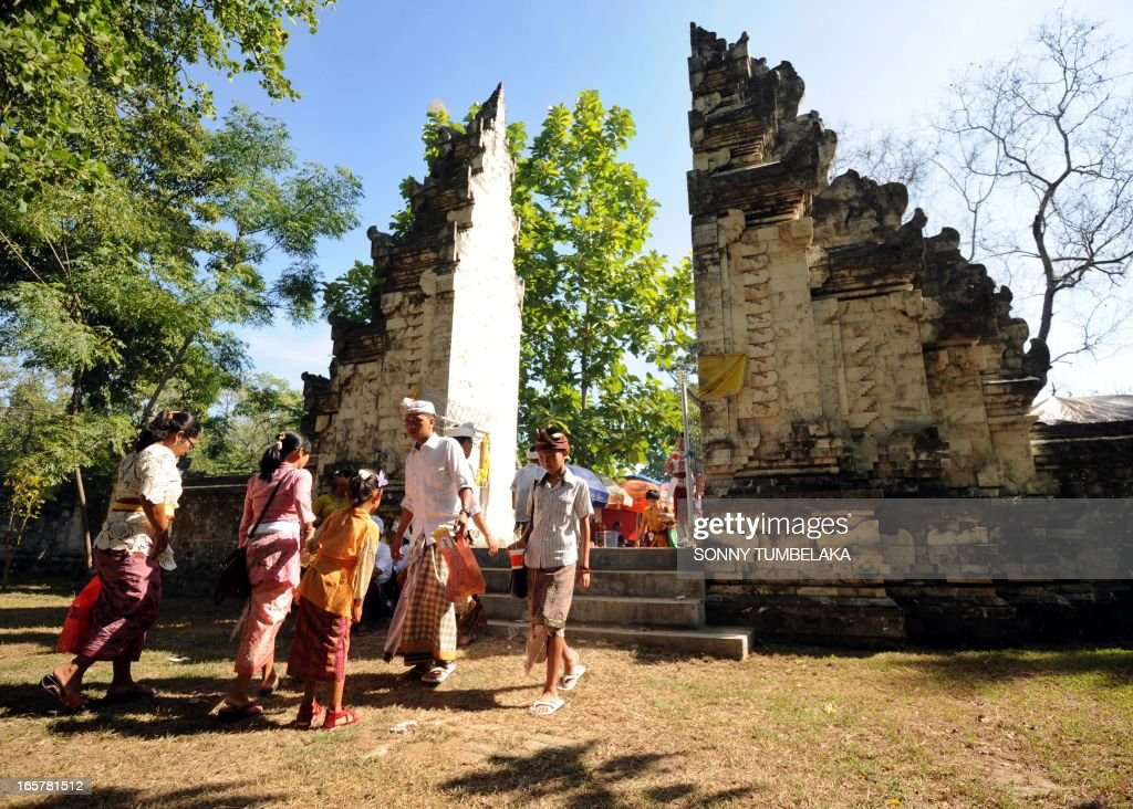 Balinese people walk after praying at a temple during the celebration of Kuningan in Denpasar on Bali island on April 6, 2013. Kuningan, the last day of the Galungan celebrations, is believed to be the ascendent day of ancestral holy spirits returning back to heaven and special offerings made of yellow rice and special dishes are offered.