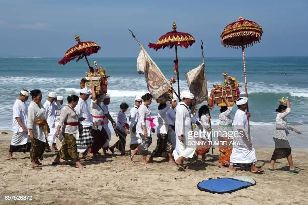 TOPSHOT Balinese people walk along Kuta beach to attend prayers for the Melasti ceremony near Denpasar on the Indonesian resort island of Bali on...
