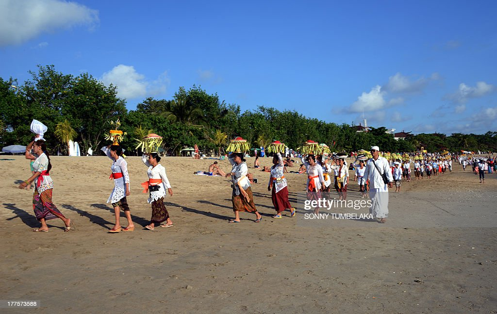 Balinese people walk near the beach during a Melasti ceremony in Kuta on the Indonesian tourist island of Bali on August 24, 2013. During the Melasti purification ceremony, villagers dress in their finest and make their way to the sea or holy springs. AFP PHOTO/Sonny TUMBELAKA