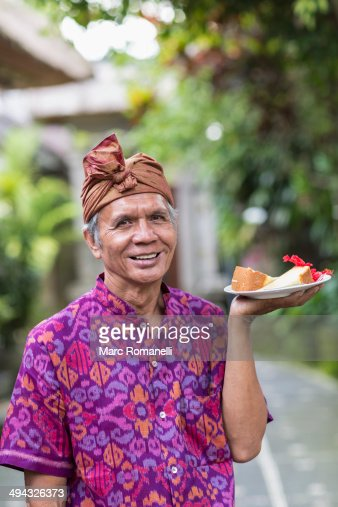 Balinese server carrying plate of food : Stock Photo