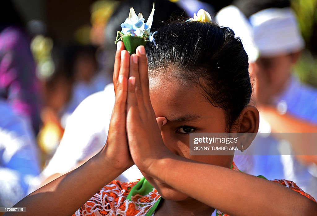 A Balinese student prays during the Hindu Saraswati holy day at a school in Denpasar on Bali island on August 10, 2013. Hindu devotees in Bali celebrated Saraswati day - the day to worship God in his manifestation as the master of all knowledge.