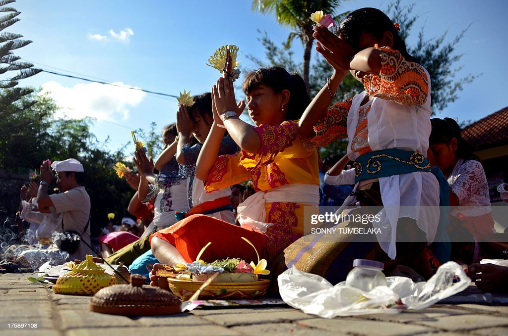 Balinese students pray during the Hindu Saraswati holy day at a school in Denpasar on Bali island on August 10, 2013. Hindu devotees in Bali celebrated Saraswati day - the day to worship God in his manifestation as the master of all knowledge.