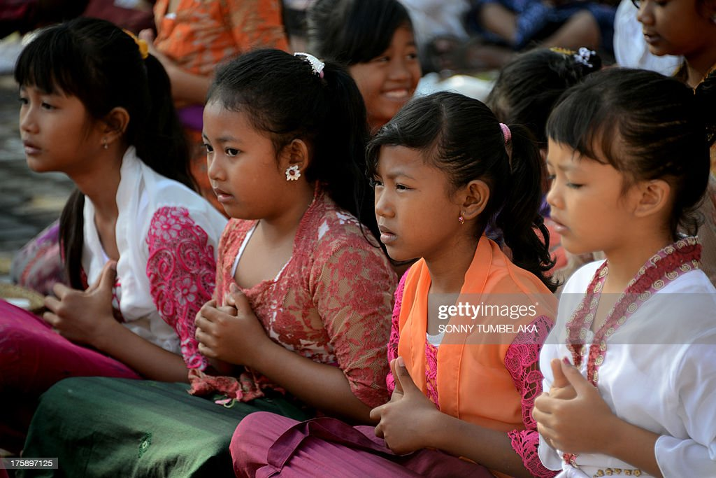 Balinese students pray during the Hindu Saraswati holy day at a school in Denpasar on Bali island on August 10, 2013. Hindu devotees in Bali celebrated Saraswati day - the day to worship God in his manifestation as the master of all knowledge. AFP PHOTO/SONNY TUMBELAKA