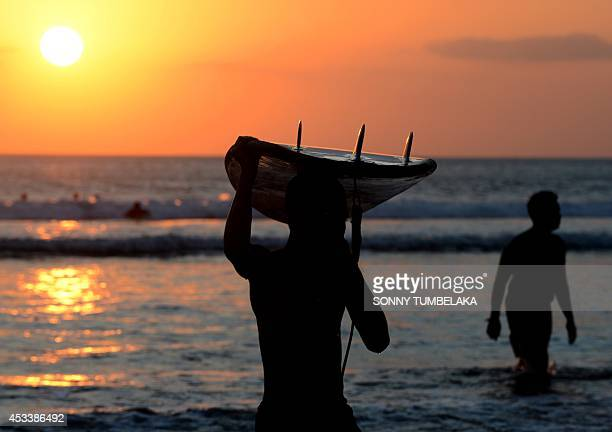 A Balinese surfer carries a surfboard as sunset along Kuta beach on the Indonesian resort island of Bali on August 9 2014 Bali is the largest tourist...