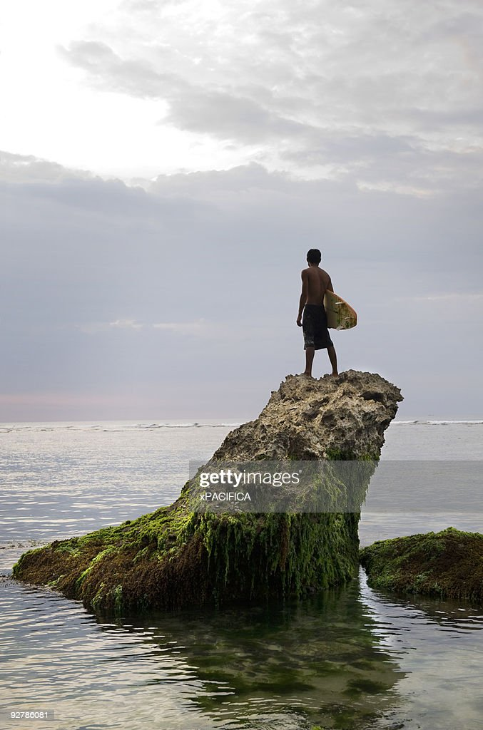 A Balinese surfer perched on top of a rock. : Stock Photo