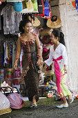 Balinese woman and girl shopping at local market. Ubud, Bali, Indonesia.