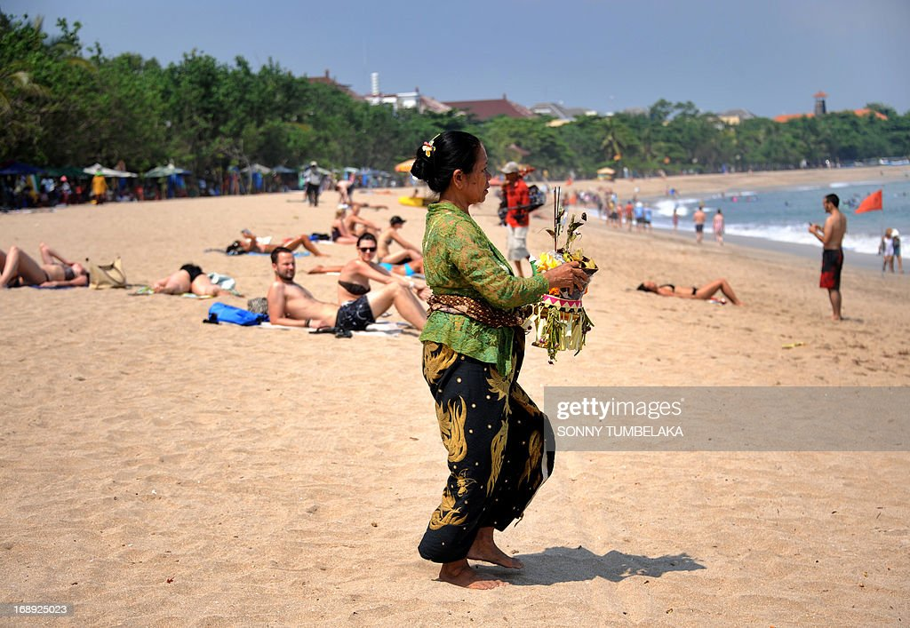A Balinese woman brings offerings to the beach as foreign tourists sunbath in Kuta on Bali island on May 17, 2013. The Indonesian government has set the ambitious target of welcoming a total of nine million foreign tourists in 2013. In 2014, it wants at least 10 million foreigners to visit Indonesia. AFP PHOTO/SONNY TUMBELAKA