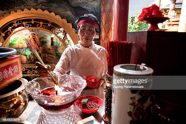 Balinese woman burns incense sticks during preparations for the upcoming Chinese New Year at Dwipayana Tanah Kilap Temple on January 25 2014 in...