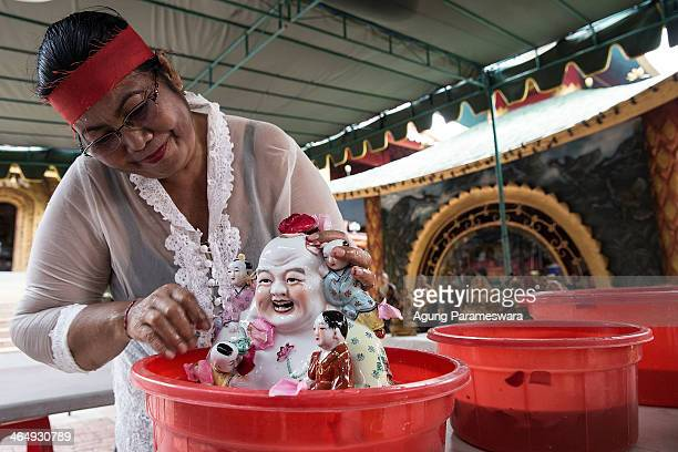 Balinese woman cleans a statue during preparations for the upcoming Chinese New Year at Dwipayana Tanah Kilap Temple on January 25 2014 in Denpasar...