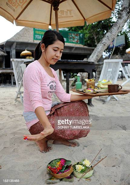 A Balinese woman prays at the Nyoman Cafe in Jimbaran on Bali island on October 1 on the seventh anniversary of the 01 October 2005 bomb blasts On 1...