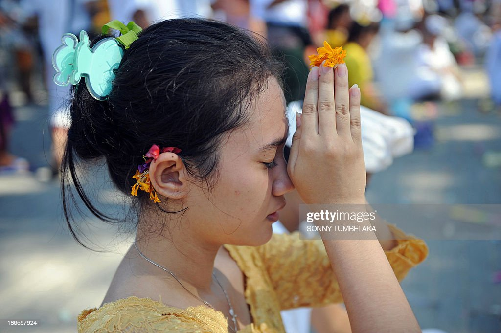 A Balinese woman prays to celebrate the holyday of Kuningan in Denpasar, Bali on November 2, 2013. Kuningan, the last day of the Galungan celebrations, is believed to be the ascendent day of ancestral holy spirits returning back to heaven and special offerings made of yellow rice and special dishes are offered.
