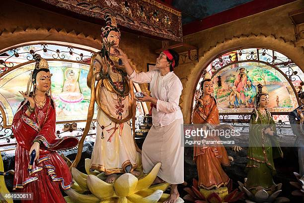 Balinese woman puts a diamond on a statue during preparations for the upcoming Chinese New Year at Dwipayana Tanah Kilap Temple on January 25 2014 in...