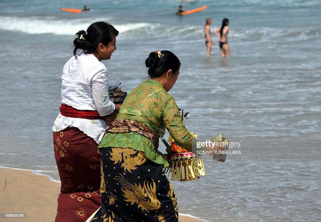 Balinese women bring offerings to the beach as foreign tourists sunbath at Kuta beach on Bali island on May 17, 2013. The Indonesian government has set the ambitious target of welcoming a total of nine million foreign tourists in 2013. In 2014, it wants at least 10 million foreigners to visit Indonesia.