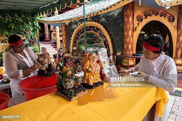 Balinese women clean statues during preparations for the upcoming Chinese New Year at Dwipayana Tanah Kilap Temple on January 25 2014 in Denpasar...