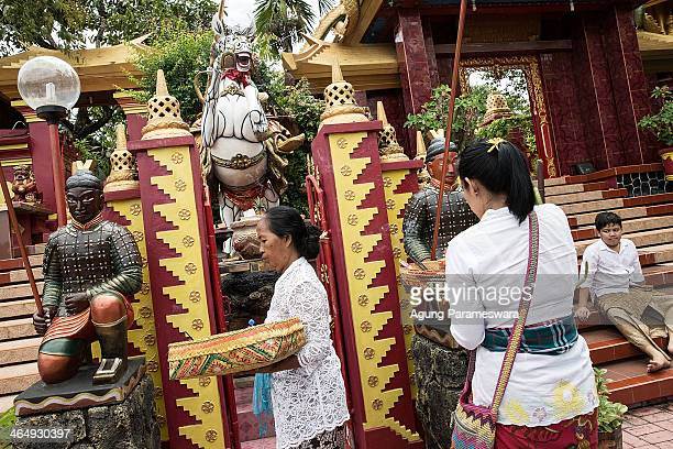 Balinese women give offerings during preparations for the upcoming Chinese New Year at Dwipayana Tanah Kilap Temple on January 25 2014 in Denpasar...