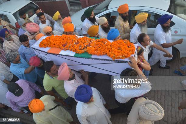 Baljit Kaur and her son Amritbir Singh carry the coffin of her husband Indian Central Reserve Police Force personnel Raghbir Singh at his funeral in...