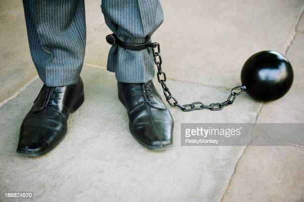 Ball and Chain Businessman Stands on Stone Background
