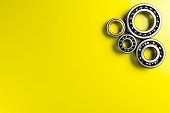 Ball bearing lying on a yellow background with copy space on the left side. Flat view from above.