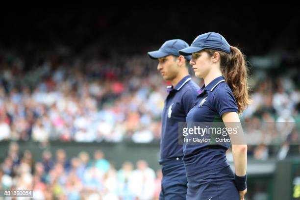 A ball boy and ball girl in action on Center Court during the Wimbledon Lawn Tennis Championships at the All England Lawn Tennis and Croquet Club at...