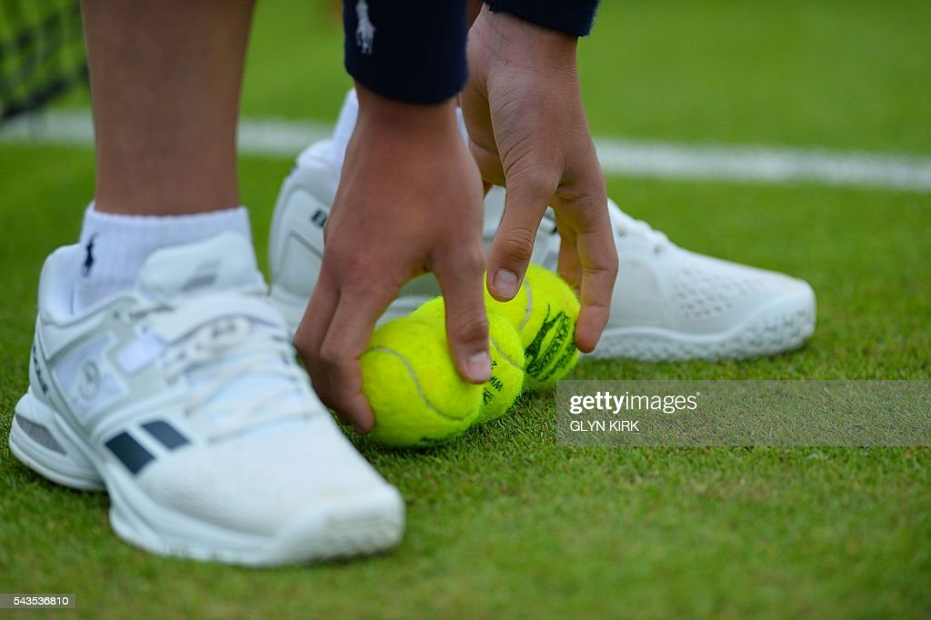 A ball boy collects tennis balls on the third day of the 2016 Wimbledon Championships at The All England Lawn Tennis Club in Wimbledon, southwest London, on June 29, 2016. / AFP / GLYN