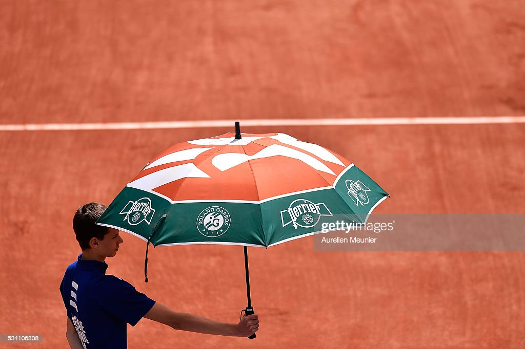 A ball boy holds an umbrella during day four of the 2016 French Open at Roland Garros on May 25, 2016 in Paris, France.