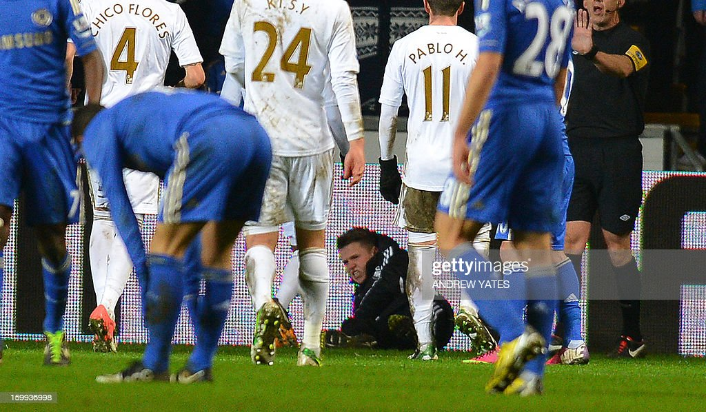 """A ball boy (C) lies on the ground as he reacts after an altercation with Chelsea's Belgium midfielder Eden Hazard during the English League Cup semi-final second leg football match between Swansea City and Chelsea at The Liberty stadium in Cardiff, south Wales on January 23, 2013. After the incident Hazard was sent off by referee Chris Foy. USE. No use with unauthorized audio, video, data, fixture lists, club/league logos or """"live"""" services. Online in-match use limited to 45 images, no video emulation. No use in betting, games or single club/league/player publications."""
