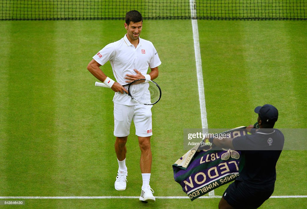 A ball boy offers <a gi-track='captionPersonalityLinkClicked' href=/galleries/search?phrase=Novak+Djokovic&family=editorial&specificpeople=588315 ng-click='$event.stopPropagation()'>Novak Djokovic</a> of Serbia a towel during the Men's Singles second round match against Adrian Mannarino of France on day three of the Wimbledon Lawn Tennis Championships at the All England Lawn Tennis and Croquet Club on June 29, 2016 in London, England.