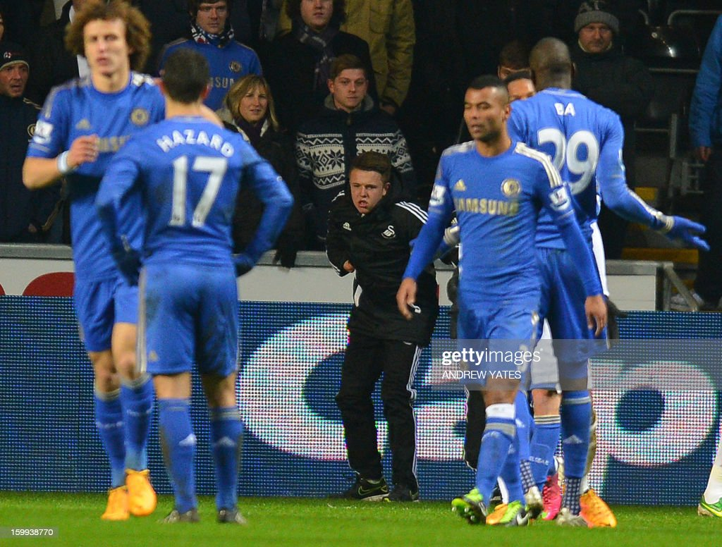 "A ball boy (C) picks himself up off the ground after being involved in an altercation with Chelsea's Belgium midfielder Eden Hazard during the English League Cup semi-final second leg football match between Swansea City and Chelsea at The Liberty stadium in Cardiff, south Wales on January 23, 2013. Hazard was sent off after the incident. USE. No use with unauthorized audio, video, data, fixture lists, club/league logos or ""live"" services. Online in-match use limited to 45 images, no video emulation. No use in betting, games or single club/league/player publications."