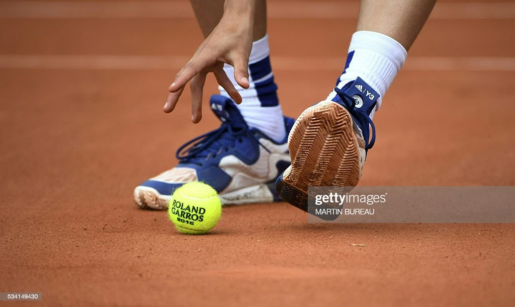 A ball boy picks up a ball during the men's second round match between Croatia's Ivan Dodig's and Spain's Fernando Verdasco at the Roland Garros 2016 French Tennis Open in Paris on May 25, 2016. / AFP / MARTIN