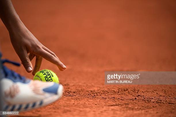 A ball boy picks up a ball on the court during a men's third round match at the Roland Garros 2016 French Tennis Open in Paris on May 27 2016 / AFP /...