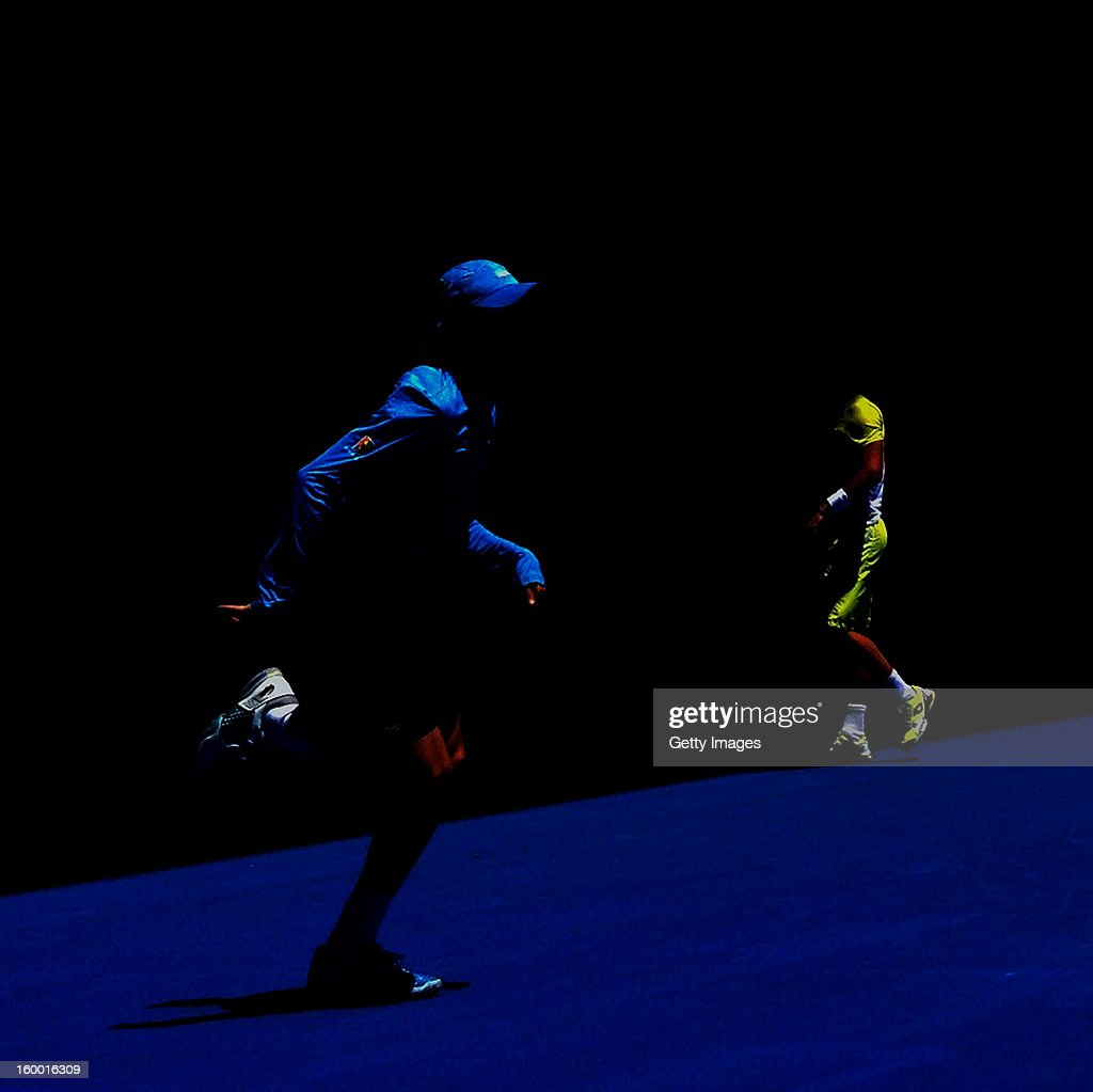A ball boy runs on court as Nicolas Almagro of Spain takes a towel break in his Quarterfinal match against David Ferrer of Spain during day nine of the 2013 Australian Open at Melbourne Park on January 22, 2013 in Melbourne, Australia.