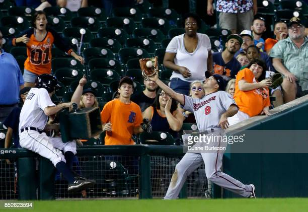 A ball boy tumbles back against the railing as Zack Granite of the Minnesota Twins catches a foul fly ball hit by Dixon Machado of the Detroit Tigers...
