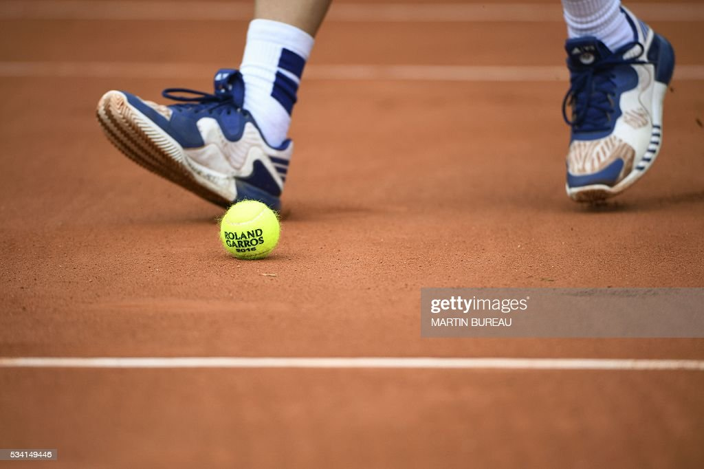 A ball boy walks nex to a ball during the men's second round match between Croatia's Ivan Dodig's and Spain's Fernando Verdasco at the Roland Garros 2016 French Tennis Open in Paris on May 25, 2016. / AFP / MARTIN