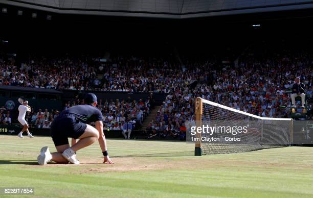 A ball boy watches Roger Federer of Switzerland in action against Thomas Berdych of the Czech Republic in the Gentlemen's Singles Semifinal of the...