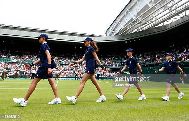 Ball boys and ball girls enter centre court during day one of the Wimbledon Lawn Tennis Championships at the All England Lawn Tennis and Croquet Club...