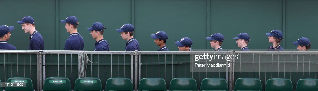 Ball boys and ball girls line up to enter a court on day four of the Wimbledon Lawn Tennis Championships at the All England Lawn Tennis and Croquet Club on June 27, 2013 in London, England.