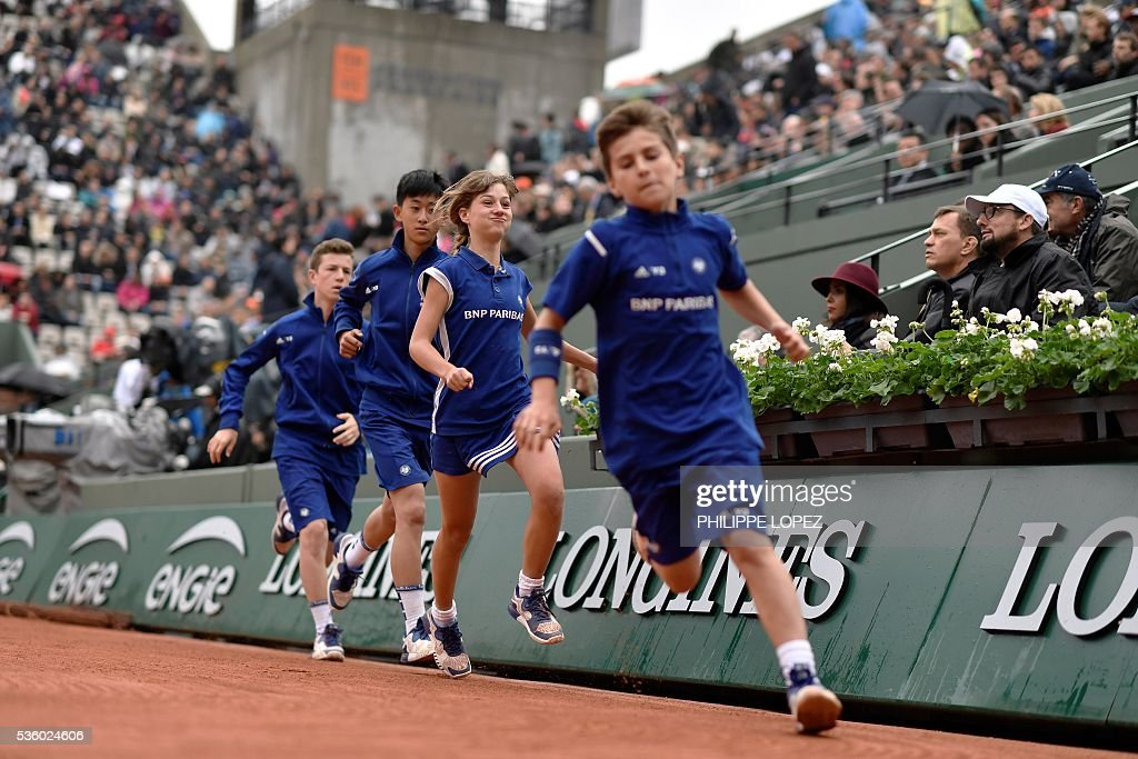 Ball boys and girls run during a women's fourth round match at the Roland Garros 2016 French Tennis Open in Paris on May 31, 2016. / AFP / PHILIPPE