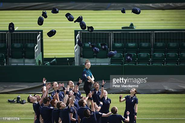Ball boys and girls throw their hats in the air during a photo shoot on day four of the Wimbledon Lawn Tennis Championships at the All England Lawn...