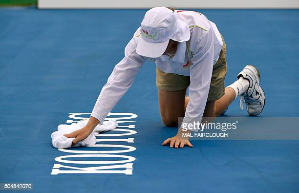 A ball boys dries the court during a rain delay on day three of the Kooyong Classic tennis tournament in Melbourne on January 14 2016 AFP PHOTO / Mal...