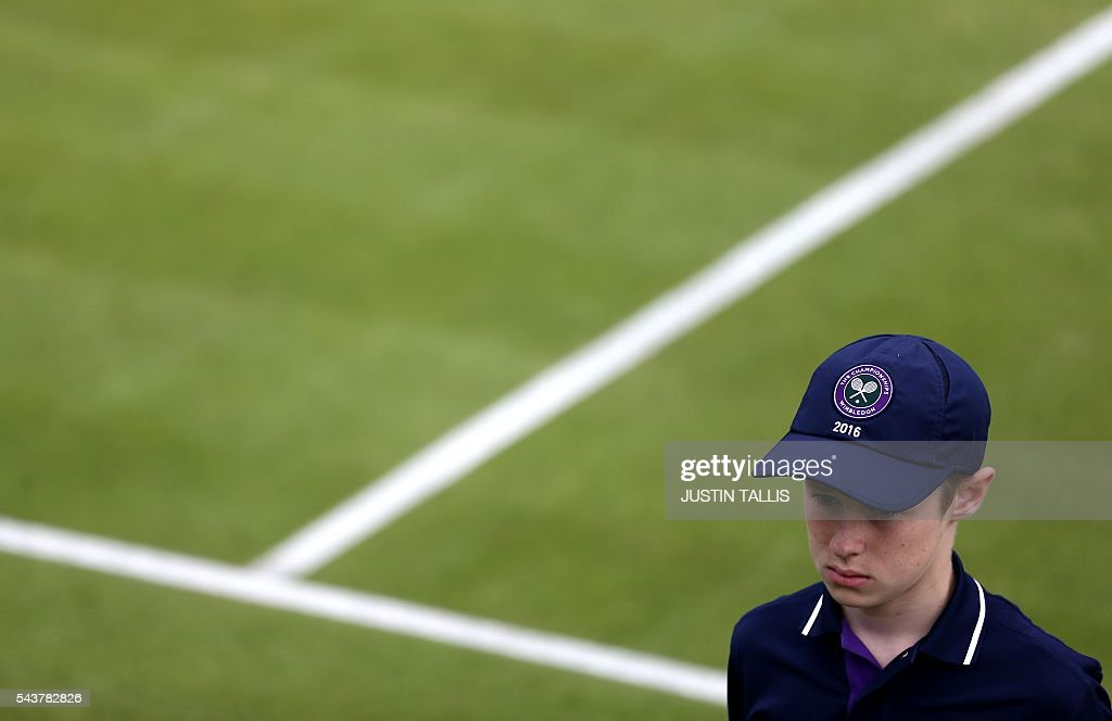 Ball boys in action on the fourth day of the 2016 Wimbledon Championships at The All England Lawn Tennis Club in Wimbledon, southwest London, on June 30, 2016. / AFP / JUSTIN