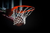 Side view of basketball hoop with ball on black background.