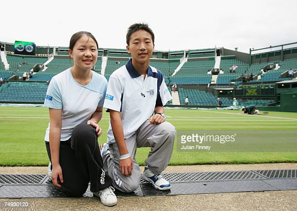 A ball girl and boy invited from Shanghai in China pose on Centre Court before participating in the event during day three of the Wimbledon Lawn...
