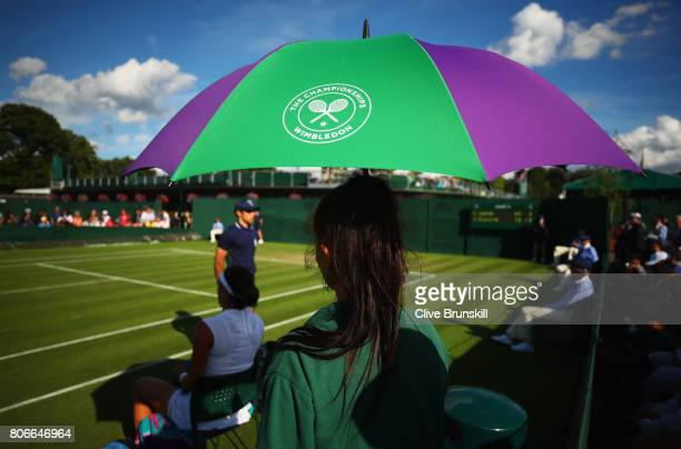 A ball girl holds an umbrella to shield players from the sun on day one of the Wimbledon Lawn Tennis Championships at the All England Lawn Tennis and...