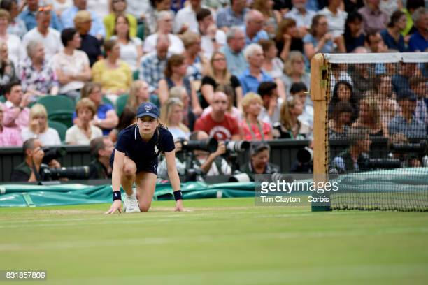 A ball girl in action on Center Court during the Wimbledon Lawn Tennis Championships at the All England Lawn Tennis and Croquet Club at Wimbledon on...