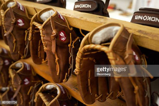 Ball gloves hang on display before being packaged at the Nokona manufacturing facility in Nocona Texas US on Thursday July 27 2017 Since the Great...