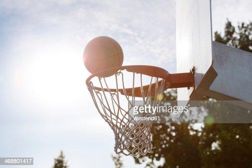 Ball going into basketball hoop