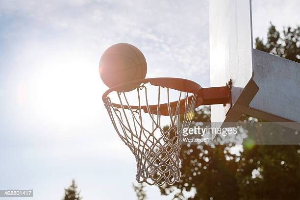 Ball going into basketball hoop